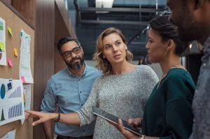 Eine Gruppe von Mitarbeitern diskutiert vor einer Pinnwand über das Thema Enterprise Content Management.