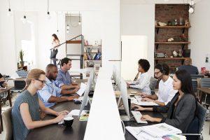 Mehrere Mitarbeiter sitzen an einem Tisch und greifen auf ein Markenportal zu.