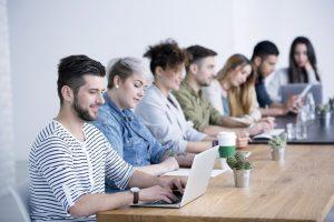 Eine Gruppe von Mitarbeitern sitzt an einem Tisch, ein Teammitglied greift mit dem Laptop auf ein Markenportal zu.
