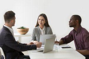 Drei Mitarbeiter sitzen an einem Tisch und diskutieren über ein Markenportal.