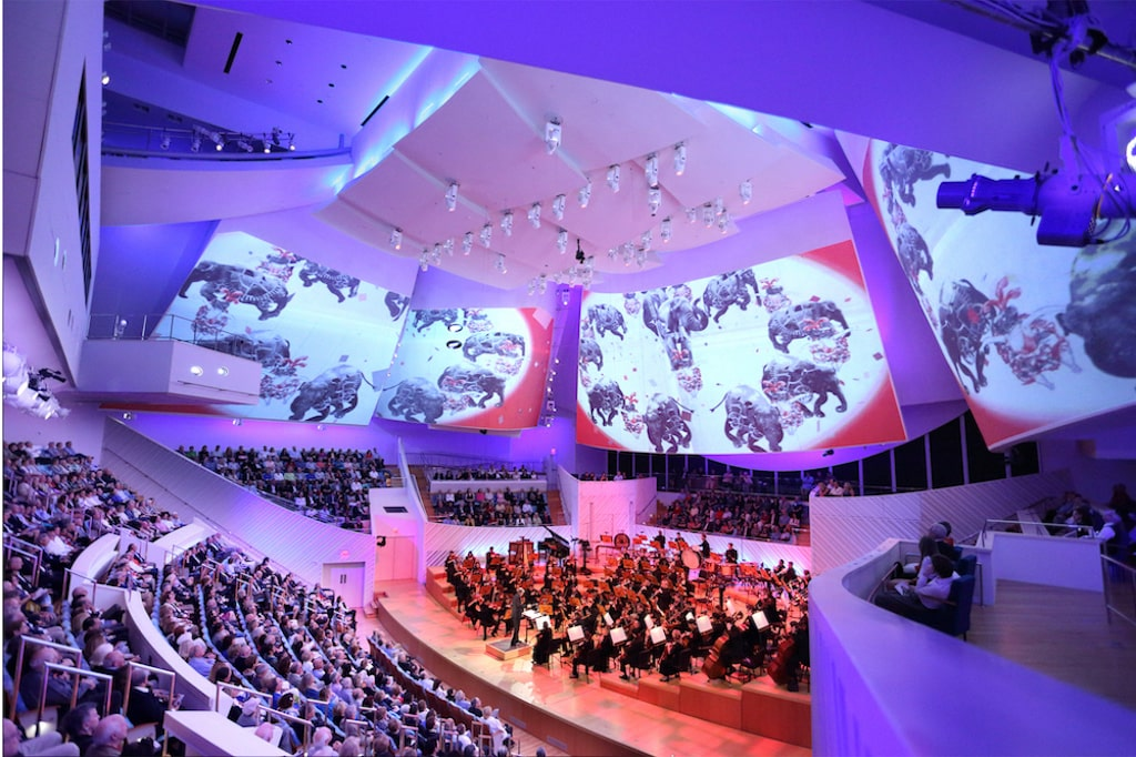 A picture of a concert hall with orchestra and audience.