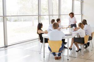 An einem Tisch sitzt eine Gruppe Arbeiter in einheitlicher Kleidung in einer Besprechung und lauscht den Ausführungen ihres Vorgesetzten zum Thema Teamarbeit-Strategien.