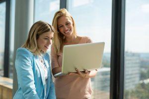 Zwei junge Mitarbeiterinnen betrachten Informationen zum Thema Teamarbeit-Strategien auf einem Laptop.
