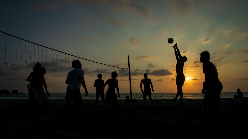 A group of people playing beach volleyball.