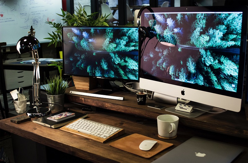 A picture of a workspace with two monitors.