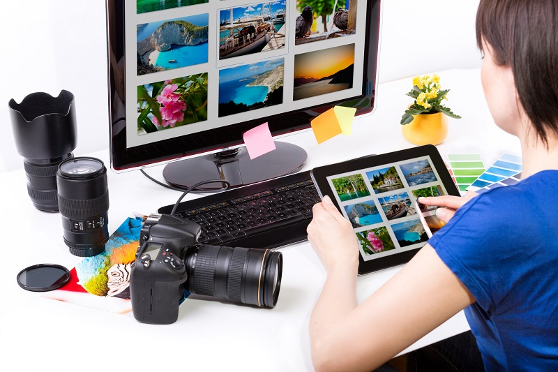 A woman browses photos on a tablet.