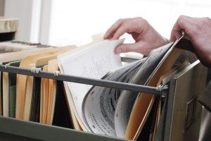 Eine Abbildung von Händen, die in einem Aktenschrank verschiedene Papiere durchgehen.
