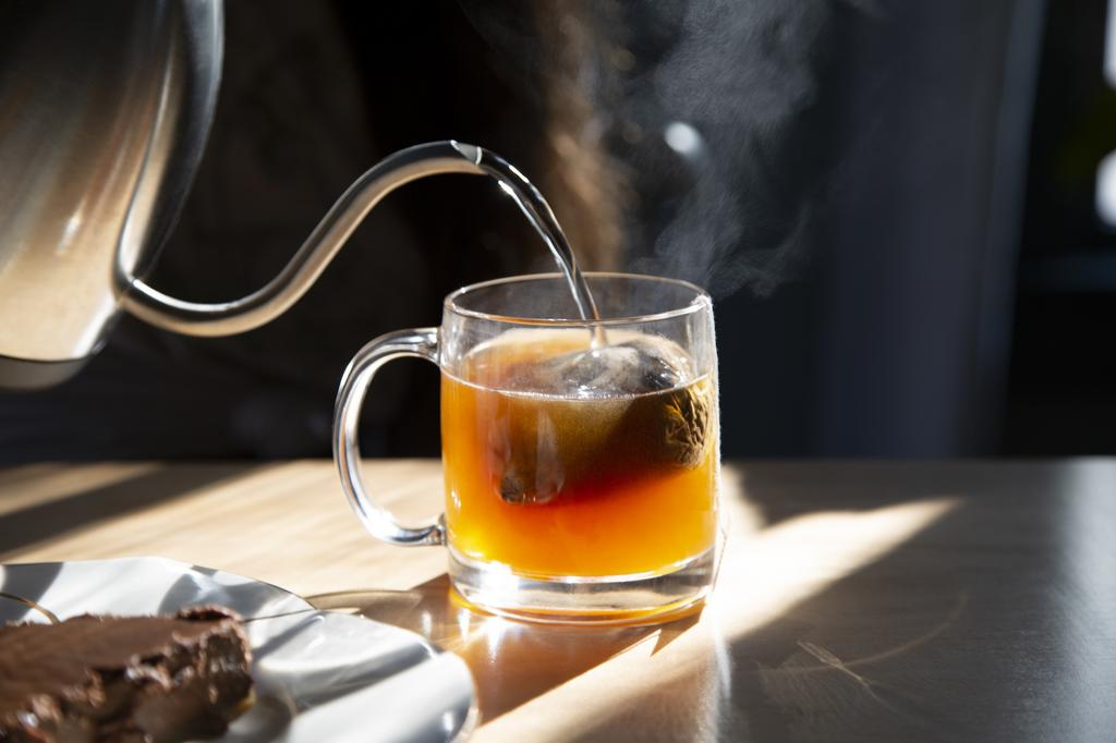 A photograph of hot water being poured onto a tea bag.