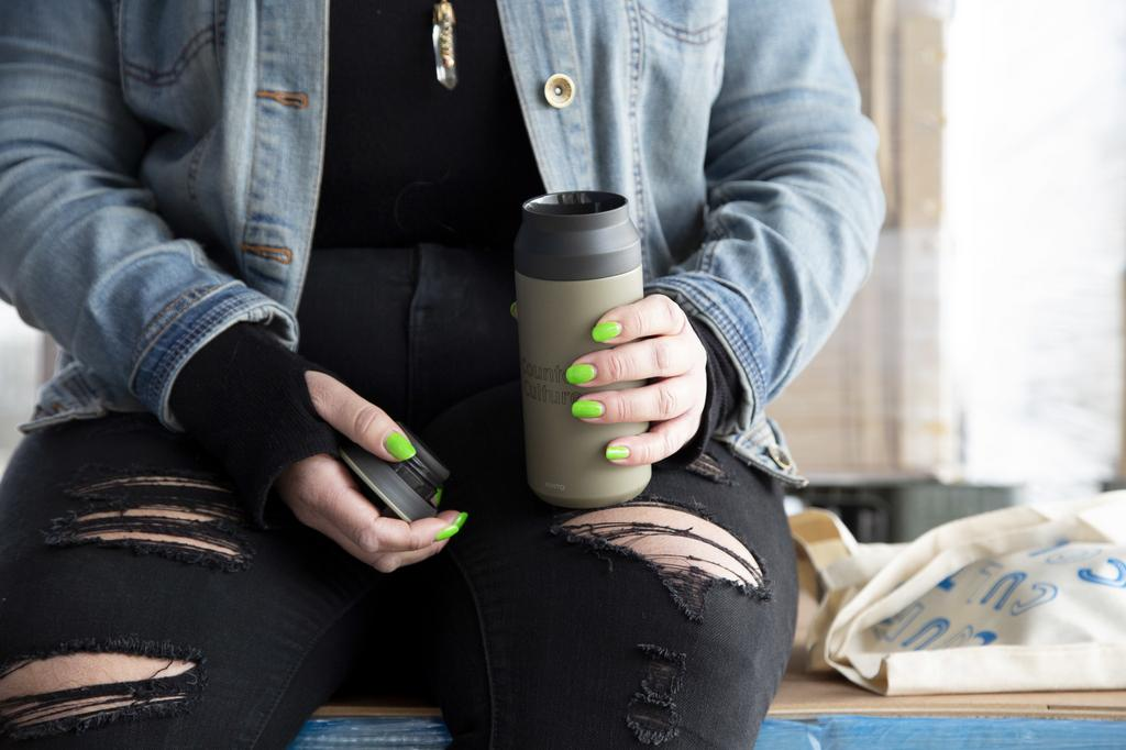 A photo of a person holding a thermos.