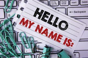 Ein Namensschild, das symbolisch für die Dateibenennungskonventionen auf einem Laptop liegt.