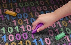 Eine Person schreibt mit bunter Kreide einen Binärcode aus Nullen und Einsen, was der Sprache für digitale Speichereinheiten entspricht.