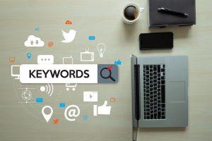 Ein Schreibtisch mit einem Notizblock, einer Tasse Kaffee, einem Smartphone und einem Laptop, neben dem das Wort 'Schlagwort' geschrieben steht.