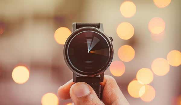 Eine Person, die eine Armbanduhr in der Hand hält.