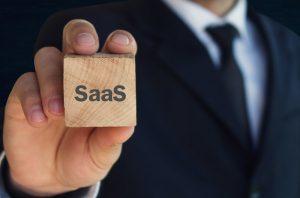 Ein Geschäftsmann hält einen Holzwürfel, auf dem das Wort 'SaaS' geschrieben steht.