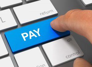Ein Finger drückt eine Taste mit der Aufschrift 'Bezahlen' auf einer Computertastatur.
