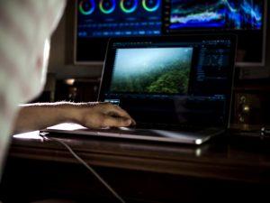 Ein Mann bearbeitet auf einem Laptop ein Video.