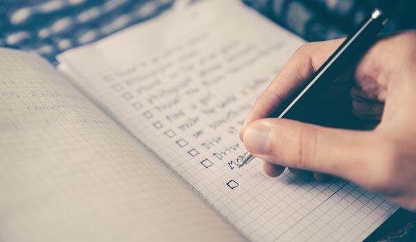 Someone writing a checklist.