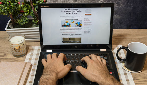 A person writing a blog post on a laptop.