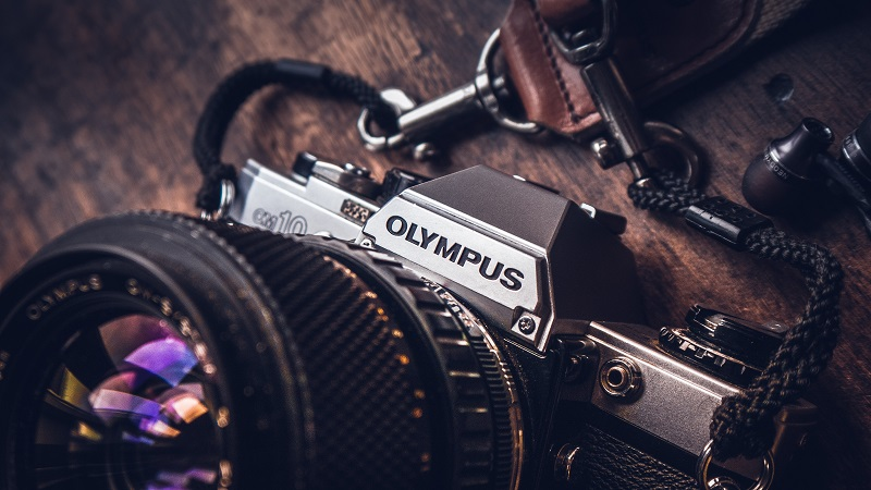 An olympus camera on a wooden desk.