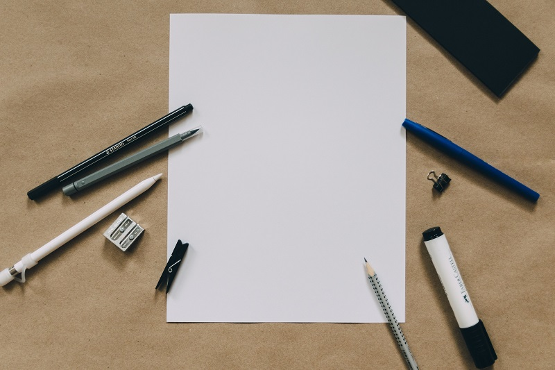 A blank sheet of paper surrounded by writing utencils.