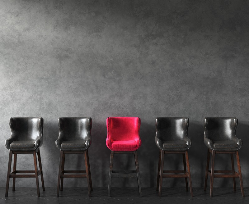 A red chair among darker chairs.