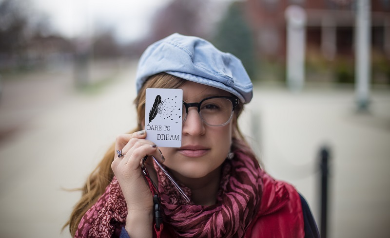 A woman holds a card in front of her eye.