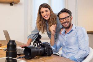 Ein junger Mann und eine junge Frau bearbeiten auf einem Laptop die Fotos einer großen Kamera.