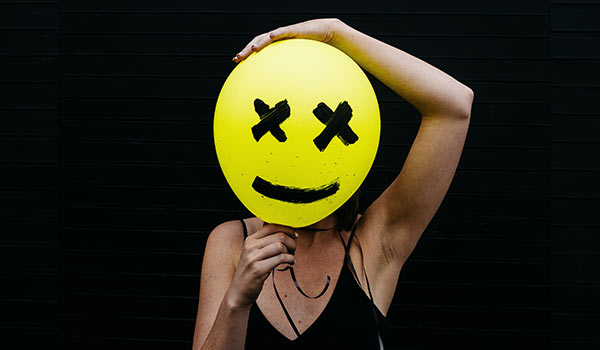 A person with a yellow smiley-face balloon in front of their face.