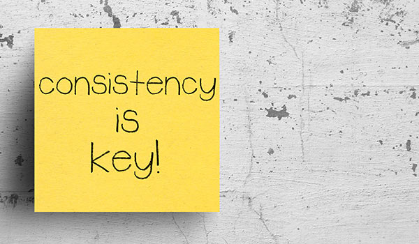 A sticky note that reads 'consistency is key'.