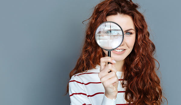 A young woman using a magnifying glass.