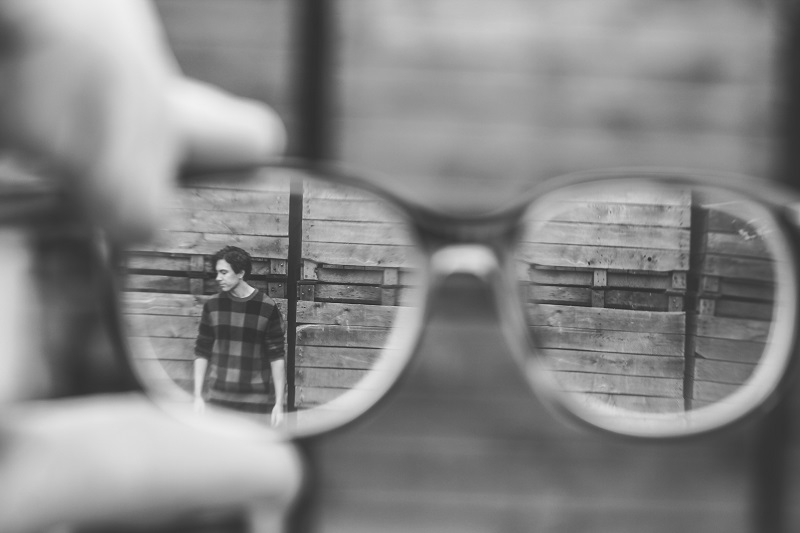 A pair of glasses viewing a man against a wall.