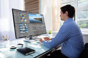 Ein Fotoorganisator sitzt an einem Computer und arbeitet.