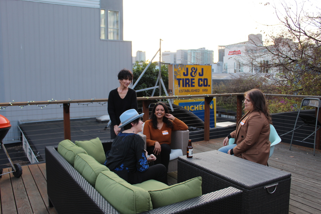 people in a conversation sitting on a rooftop terrance.