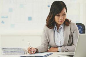 Eine Unternehmerin sitzt vor ihrem Laptop und macht sich Notizen über Konzepte zur Zusammenarbeit in Unternehmen.