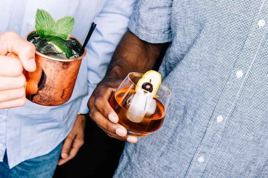 Two persons holding drinks.