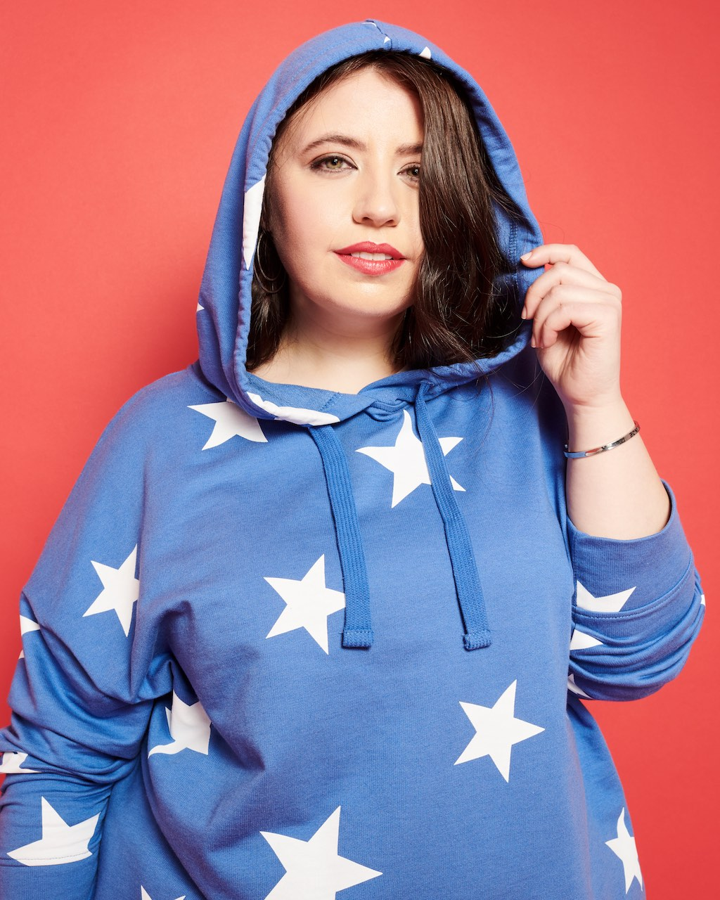 A woman wearing a hooded sweater.