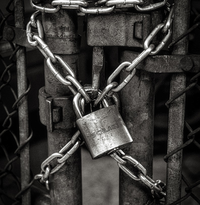 A padlock chaining a gate.