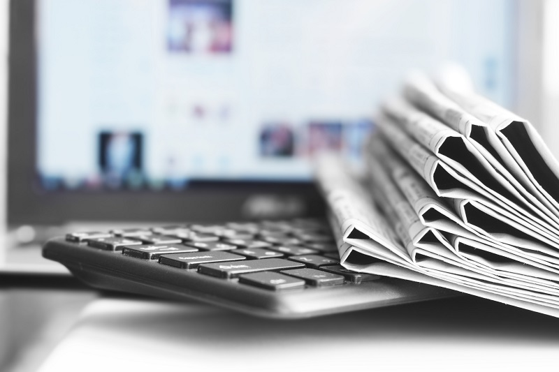 Newspapers on top of a keyboard.