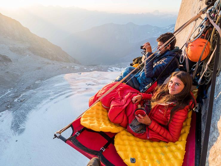 Zwei Bergwanderer machen bei einer Pause Fotoaufnahmen von der Umgebung.