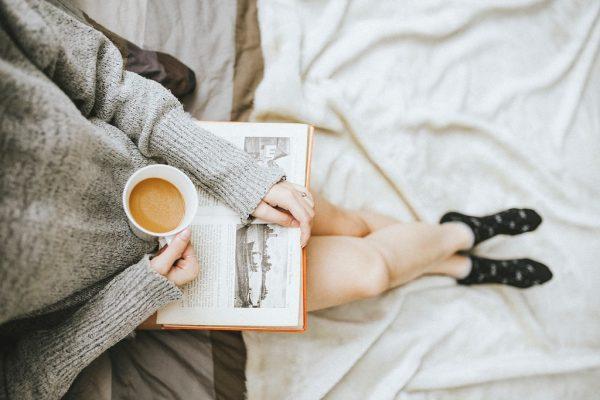 Eine sitzende Frau mit einem Buch auf dem Schoß und einem Kaffee in der Hand.