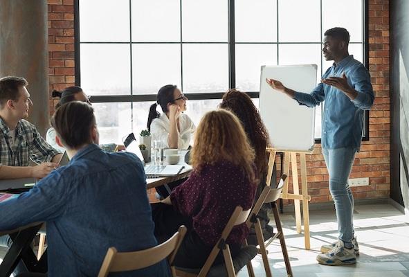 Ein junger Mann leitet eine betriebliche Besprechung zum Thema Content Lifecycle Management.