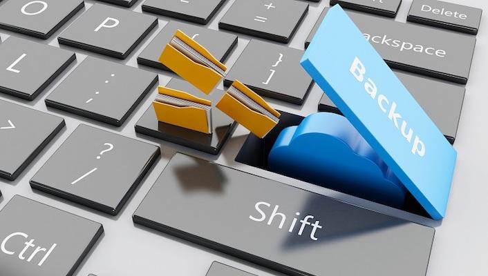 Eine Tastatur, auf der eine aufgeklappte Taste mit dem Wort Backup beschriftet ist, unter der sich ein Symbol für einen Cloud-Speicher verbirgt, auf das sich Dateisymbole zubewegen.
