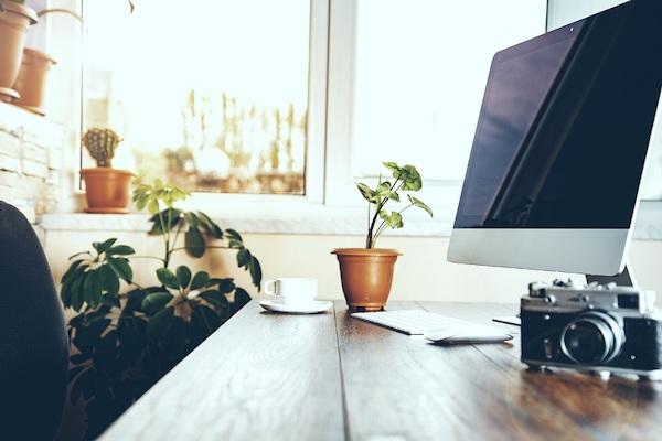 Auf einem Tisch steht eine Kamera neben einem Computermonitor.