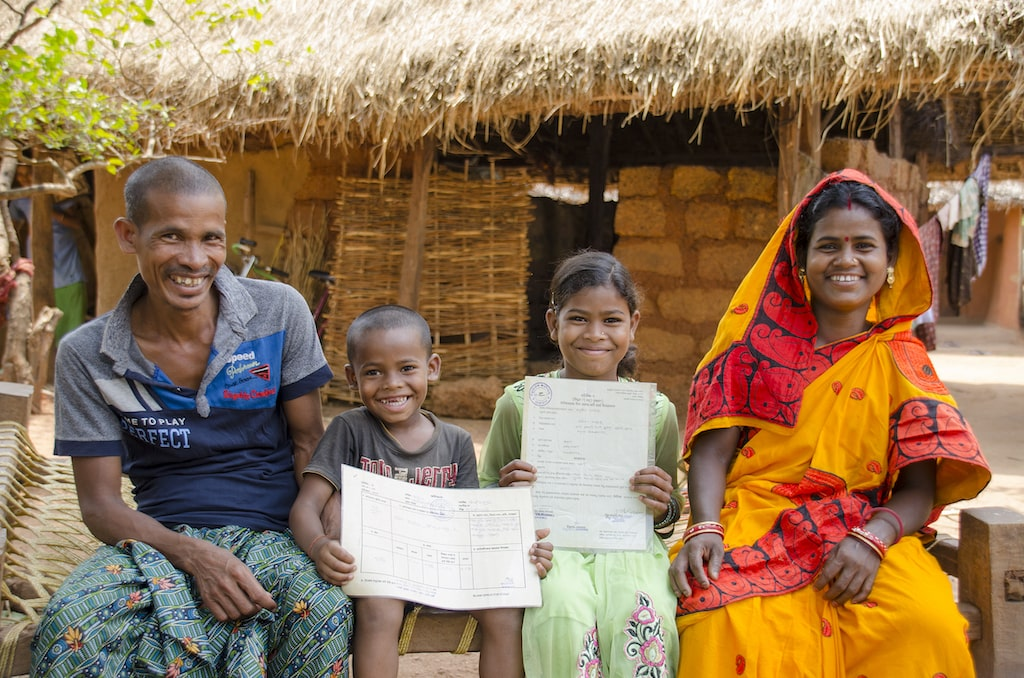 A happy family with two children sitting in a village.