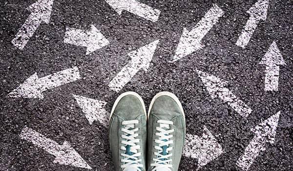 Ein Fußpaar inmitten von Pfeilen auf dem Boden.