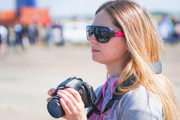 Eine junge Fotografin steht an einem Strand.