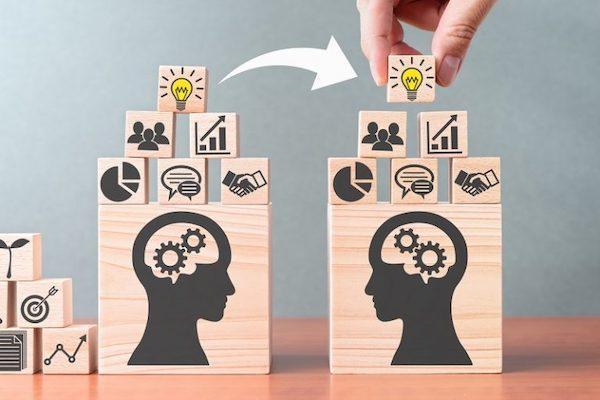 Übertragung von Wissen zwischen zwei Personen wird mithilfe von Holzklötzen veranschaulicht, die Elemente einer Wissensdatenbank sind.