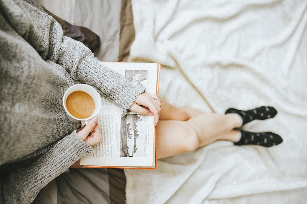 A person drinking coffee and reading a book.