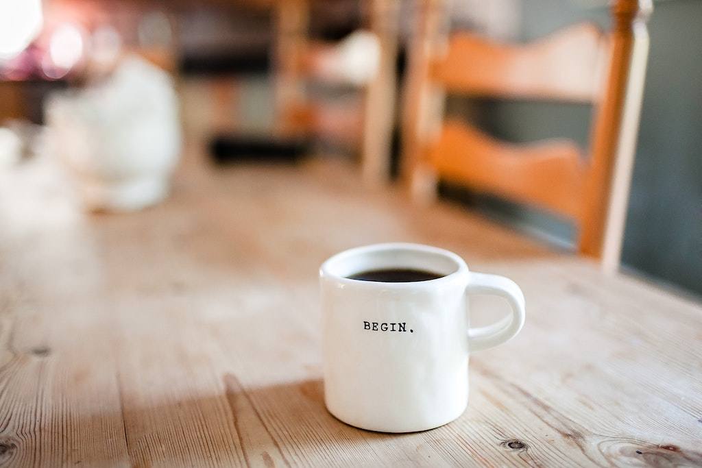 A coffee cup that reads 'Begin'.