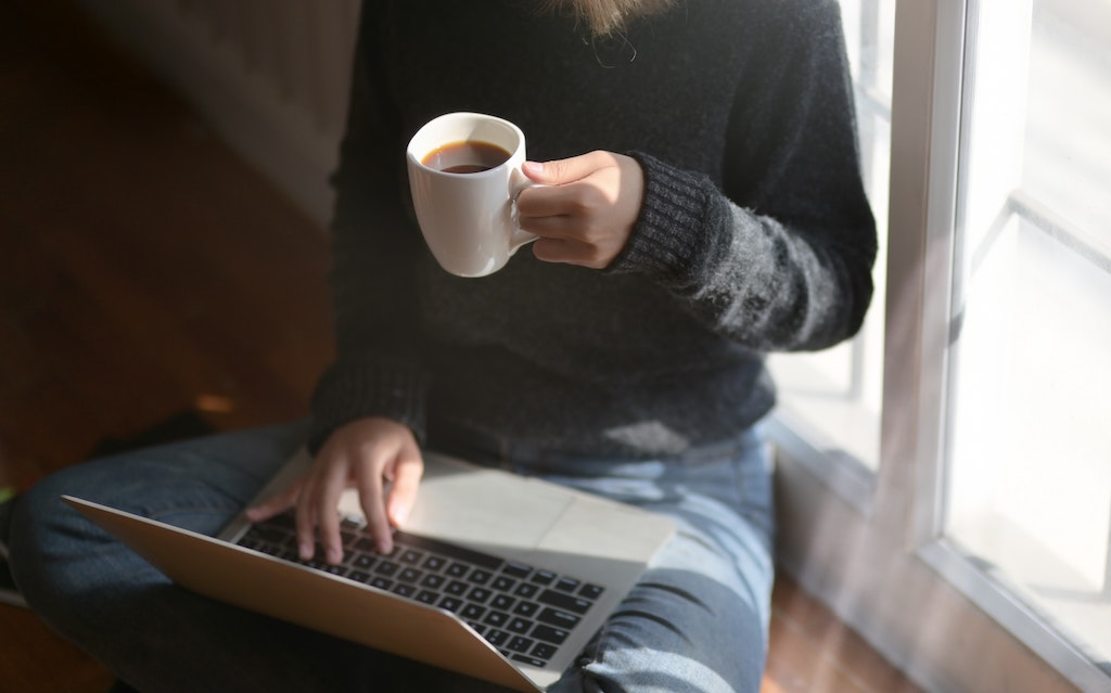 A woman sitting at a window, working on a laptop while drinking coffee.